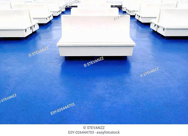 White seat or bench rows, a blue floor on a ferry boat deck as a background or a pattern