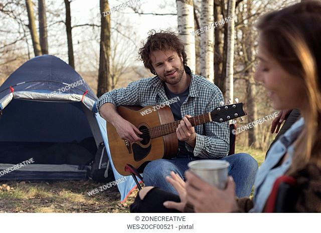 Couple camping in forest with man playing guitar