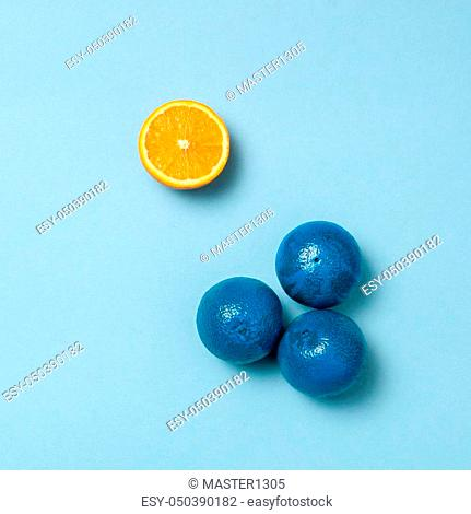 Creativity, creative thinking, ideas concept with blue mandarins and one yellow mandarin blue background. The concept - not like everyone else or concept...