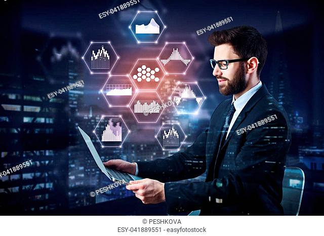Side view of young businessman using laptop on abstract night city background with business hologram. Technology, communication and media concept