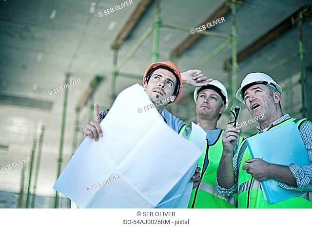Construction workers using blueprints