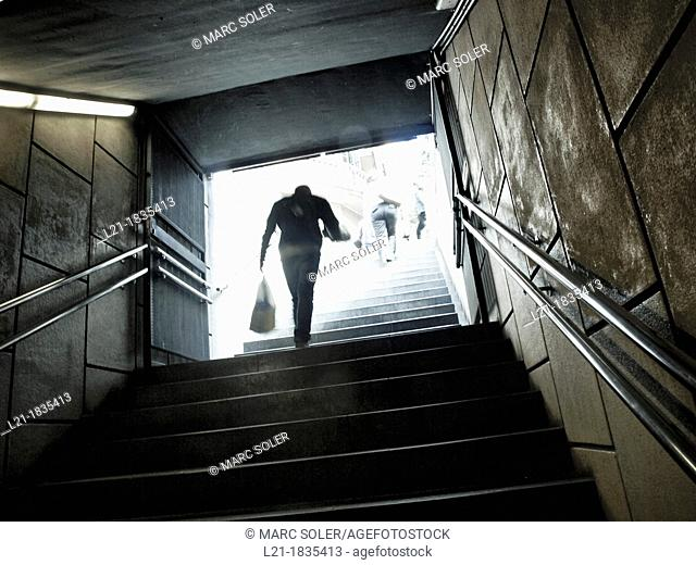 Person coming out of the metro, upstairs, carrying a bag in his hand. Barcelona, Catalonia, Spain