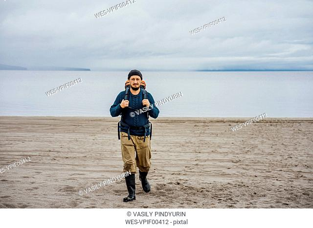 Man with backpack, walking on the beach
