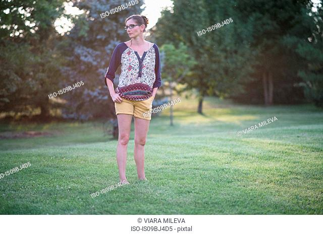 Woman standing in park at sunset