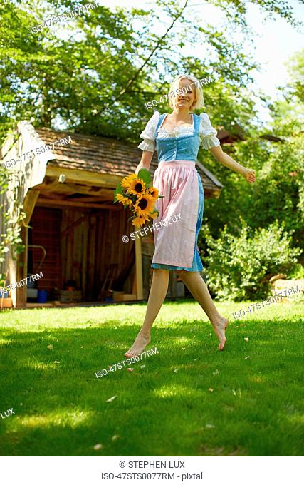 Woman carrying flowers in backyard