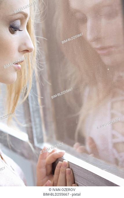 Reflection of Caucasian woman leaning on window