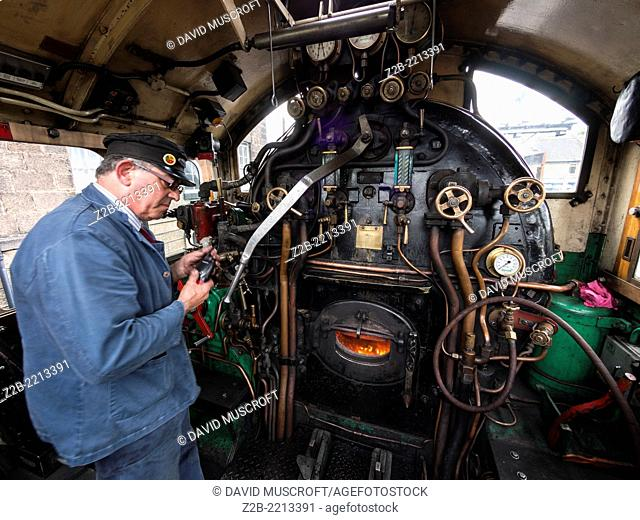 The driver and fireman of a vintage steam engine locomotive, North Yorkshire Moors Railway, on the North Yorkshire Moors, Yorkshire, UK