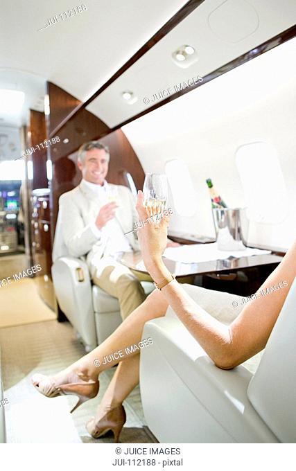 Attractive smiling couple drinking champagne on private jet