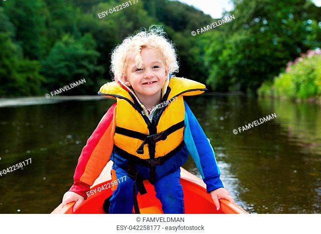 Happy kid enjoying kayak ride on beautiful river. Little curly toddler boy kayaking on hot summer day. Water sport and camping fun. Canoe for children