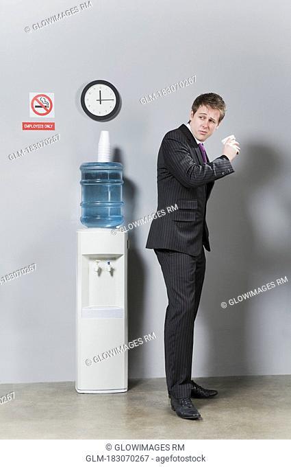 Businessman drinking water near a water cooler