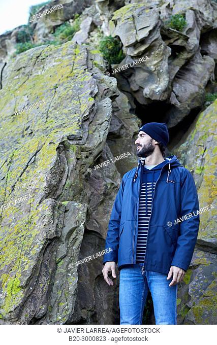 Adult man at the coast of Santa Clara Island, Donostia, San Sebastian, Gipuzkoa, Basque Country, Spain, Europe, Raincoat, Winter