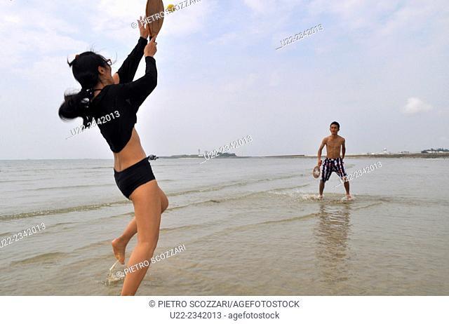 Naha, Okinawa, Japan: friends playing frescobol, Brazilian beach tennis, at Senaga-jima
