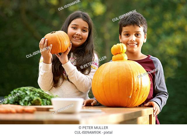 Portrait of brother and sister in garden holding up a pumpkin