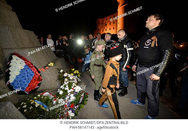Members and sympathizers of the Russian motorcycle club 'Night Wolves' place flowers as they stand in front of the Soviet cenotaph in Torgau, Germany