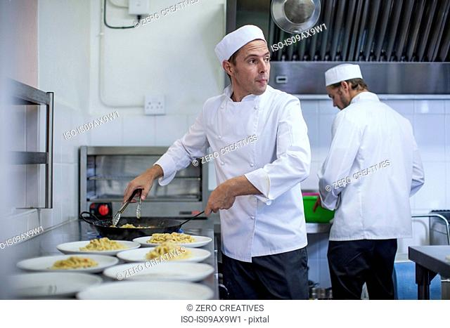 Chef filling plates with pasta in kitchen