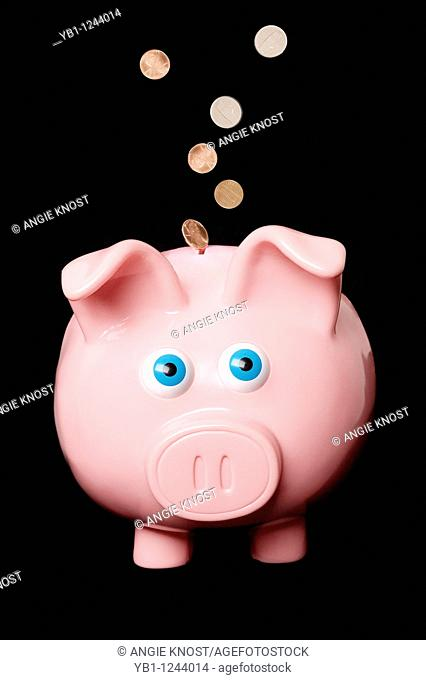 Classic pink piggy bank with American coins flying in or out