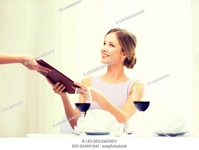 reastaurant and happiness concept - smiling young woman giving menu to waiter at restaurant