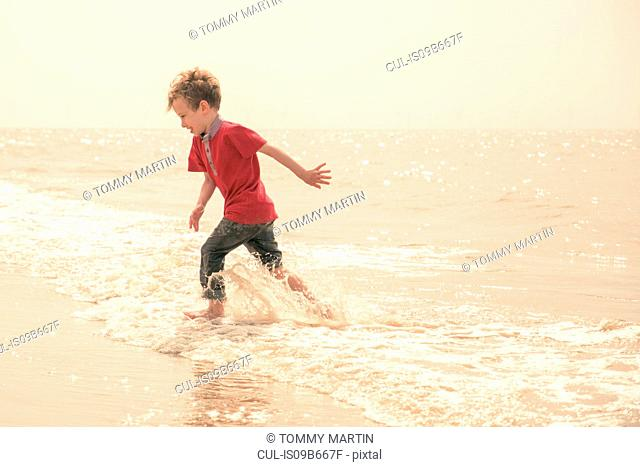 Boy running and splashing in sea