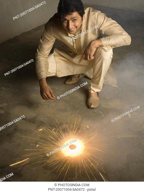 Portrait of a mid adult man crouching near a firecracker and smiling
