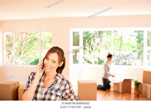 Woman talking on cell phone in new house