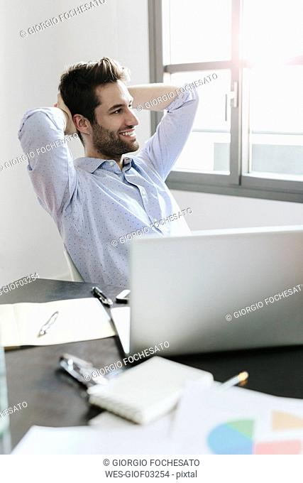Young businessman working in office, taking a break