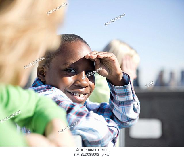 Boy on rooftop with friends shielding eyes
