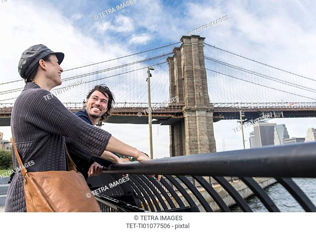 Couple leaning against railing