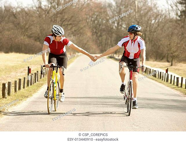 Cyclist Passing Water Bottle To Other Athlete