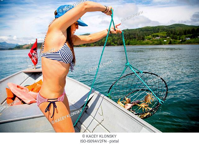 Young woman hauling in crab trap on fishing boat, Nehalem Bay, Oregon, USA