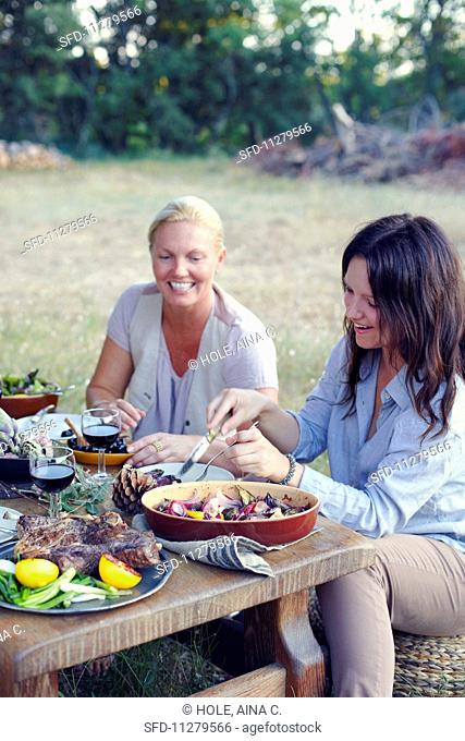 Two women eating Provençal food in a garden