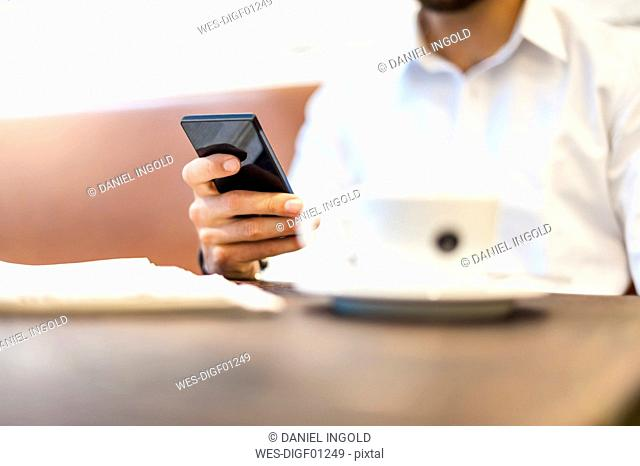 Close-up of businessman with cell phone and cup of coffee in a cafe