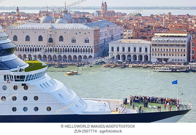 Passengers and crew on the helicopter deck of a huge cruise ship as it passes a crowded Venice waterfront, Veneto, Italy, Europe