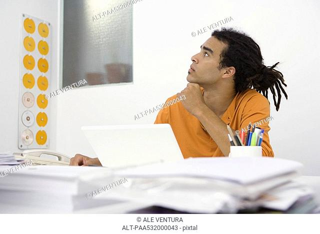 Man sitting at desk, holding chin, looking up