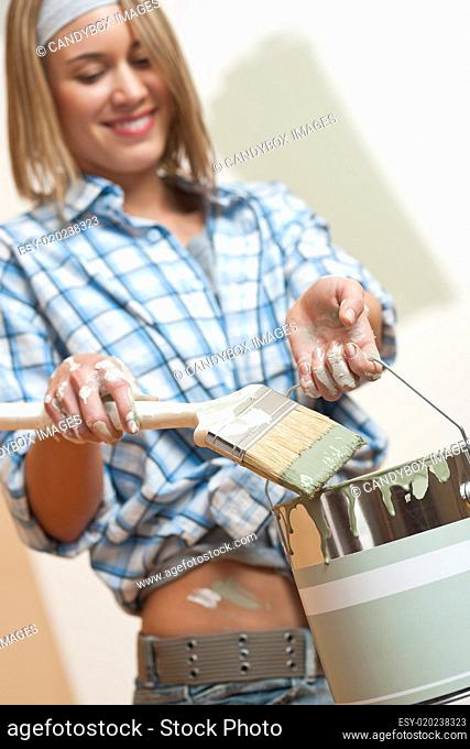 Home improvement: Smiling woman holding paint can