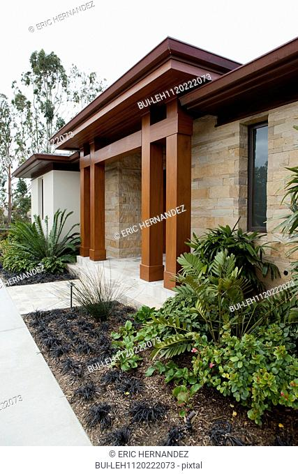 Exterior of a house with stone walls and brown pillars; Newport Beach; California; USA