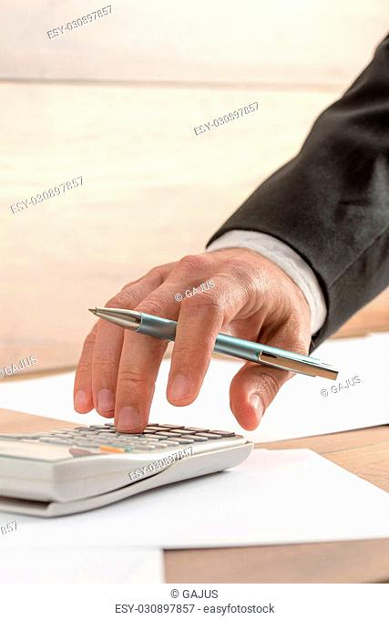 Businessman doing a calculation on a manual desk top calculator, close up of his hand holding a pen
