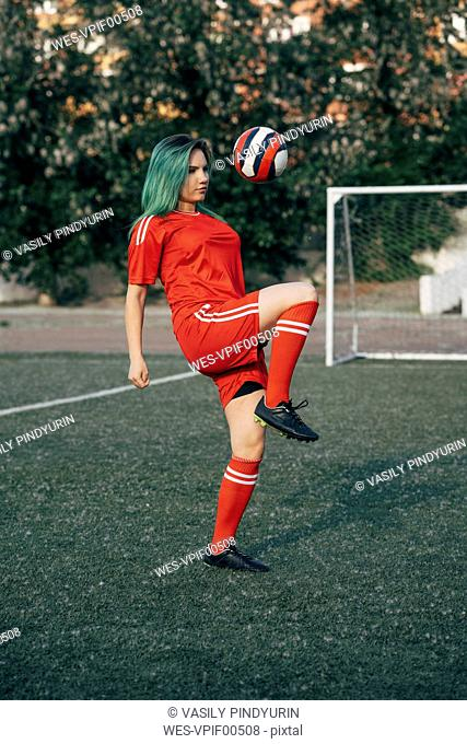 Young woman playing football on football ground balancing the ball
