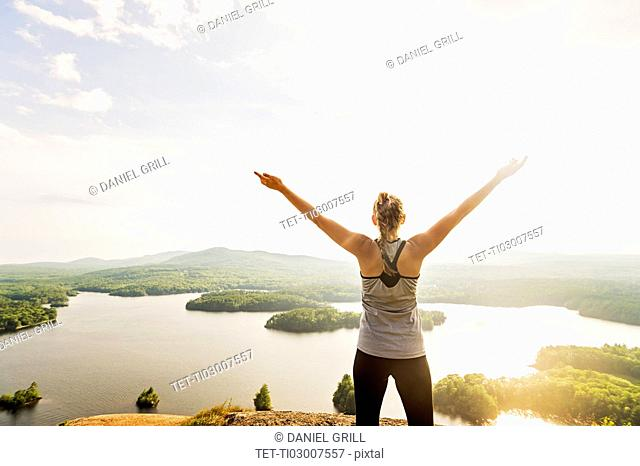 Young woman standing on top of mountain with outstretched arms, rear view