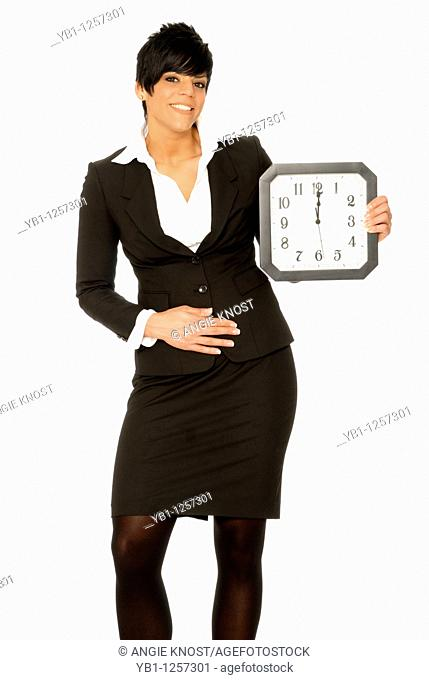 Business woman holding a clock that reads 12 o'clock, and gesturing to her stomach  Can represent lunchtime hunger
