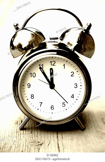 an alarm clock shows 5 minutes to 12