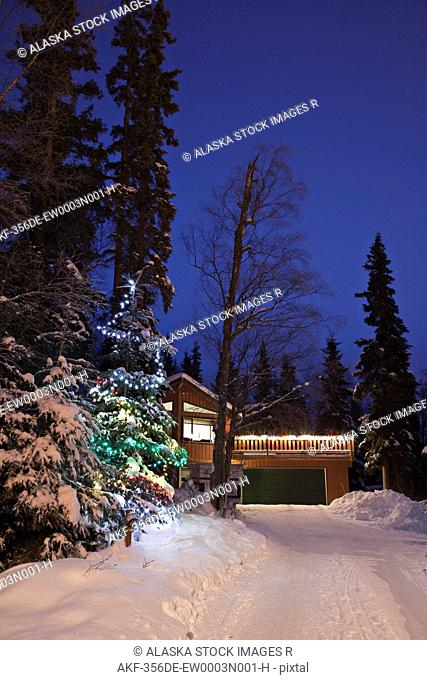 A lit Christmas tree beside a snow covered driveway with a home in the background in a forested residential area of Anchorage, Alaska
