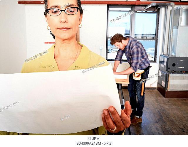 Woman looking at blueprint