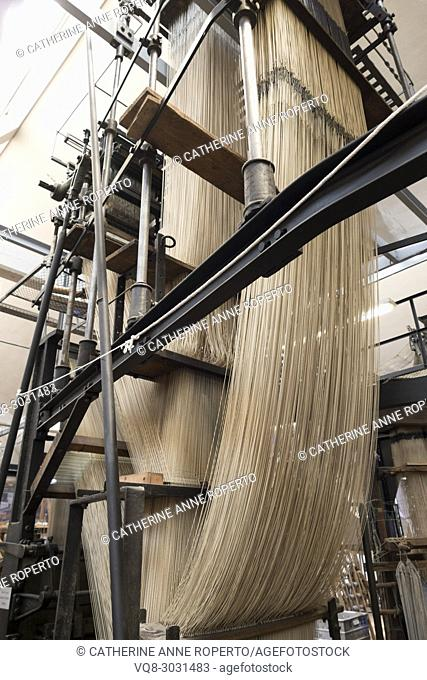 Epic cascades of thread, resembling a galleon ship in full sail, supported by wood and metal architecture of industrial revolution jacquard textile industry