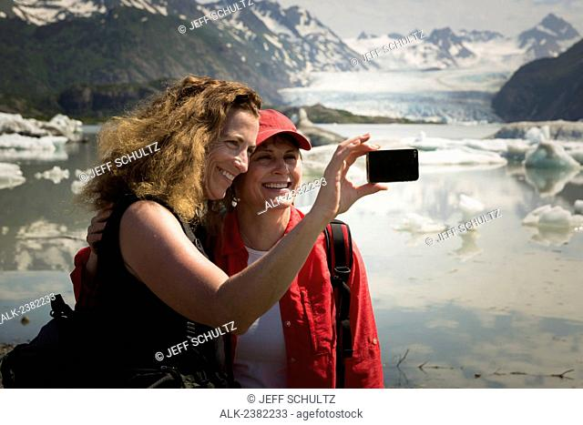 Two women taking self portrait with smart phones at Grewingk Glacier near Kachemak Bay near Homer, Alaska, Summer