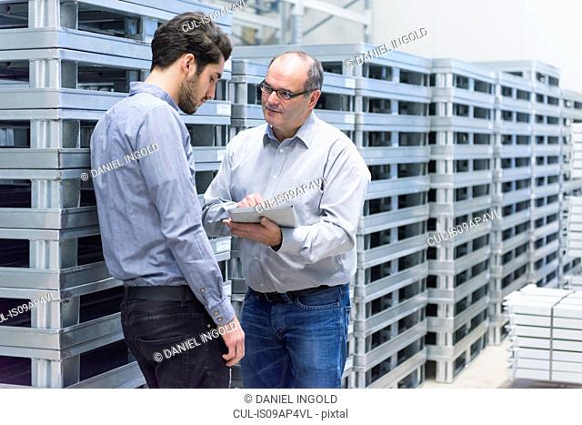 Businessman meeting worker in factory warehouse