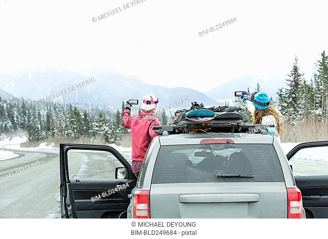 Caucasian women standing in car in winter photographing scenic view