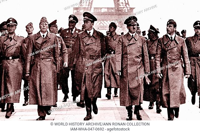 Hitler walks with Nazi officers. Hitler was an Austrian-born German politician and the leader of the Nazi Party. He was responsible for Nazi Germany