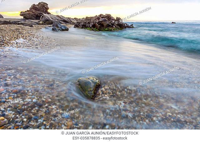 Sunrise at Wilches Beach, Torrox Coast, Malaga, Spain. Visible taro or haze at bottom