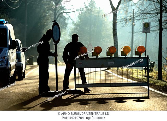Policemen block a road because of the defusing of several aerial bombs from WWII in the Dippoldiswalder Heide in Karsdorf, Germany, 12 November 2013