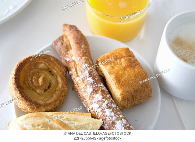 Breakfast table with coffee orange juice and pastries Spain